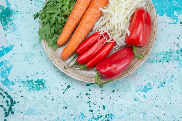 Vue de dessus de la composition de légumes frais carottes chou verts et poivrons épicés rouges sur un bureau bleu vif, repas de légumes sains