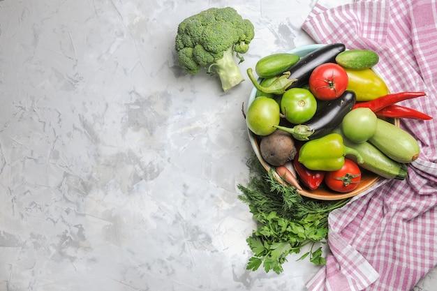 Vue de dessus de la composition de légumes frais à l'intérieur de la plaque sur fond blanc