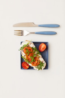 Vue de dessus à composition minimale de bruschetta unique avec des tomates cerises et des herbes à côté d'un couteau et d'une fourchette, petit-déjeuner sain et concept de régime