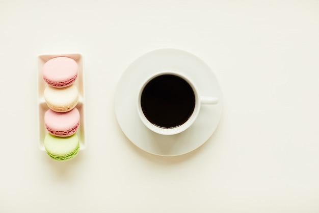 Vue de dessus à composition minimale de café noir et macarons sur table de café blanc