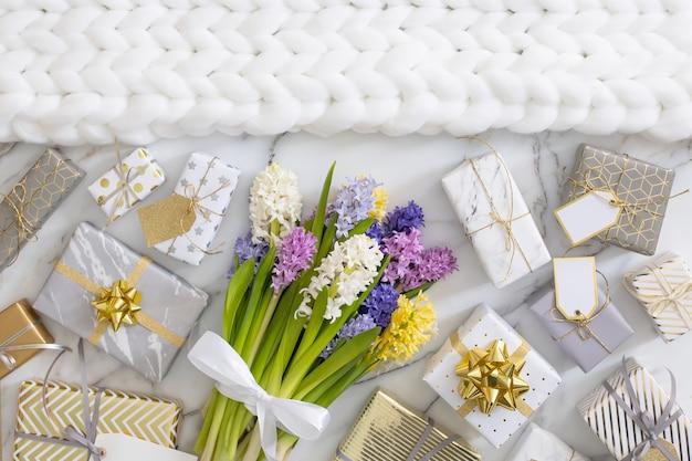 Vue de dessus composition à la mode avec des coffrets cadeaux emballés festifs noeud de ruban décoré de fleurs en fleurs