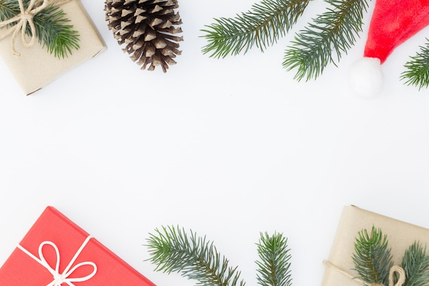 Vue de dessus de la composition de noël, boîte de cadeau, pommes de pin, branches de sapin sur fond blanc et espace de la copie pour l'information de texte