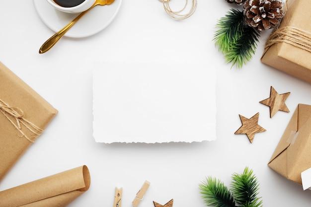Vue de dessus de la composition de noël avec boîte-cadeau, ruban, branches de sapin, cônes, anis sur tableau blanc