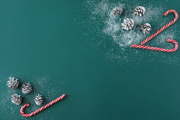 Vue de dessus de la composition de noël de cônes de sapin enneigé, décorations de bonbons rouges sur bleu vert