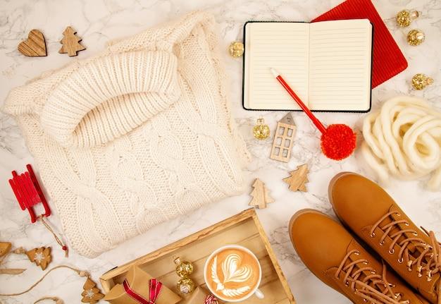 Vue de dessus sur la composition de noël avec un pull chaud, des cadeaux, des lumières de noël et du café