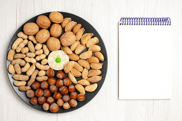 Vue de dessus composition de noix noix fraîches cacahuètes et noisettes à l'intérieur de la plaque sur un bureau blanc casse-croûte de noix arbre de nombreuses coquilles