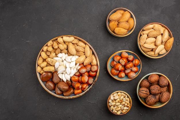Vue de dessus de la composition des noix noix fraîches à l'intérieur de pots sur une surface sombre