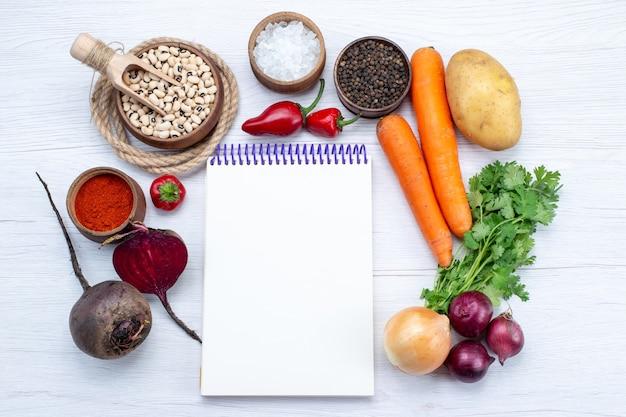Vue de dessus de la composition végétale avec des légumes frais haricots crus carottes verts bloc-notes et pommes de terre sur le bureau blanc salade de légumes repas alimentaire