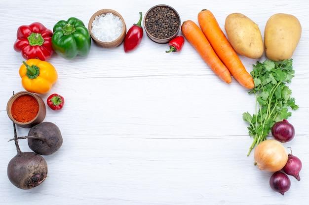 Vue de dessus de la composition végétale avec des légumes frais verts haricots crus carottes et pommes de terre sur le fond blanc repas alimentaire salade de légumes