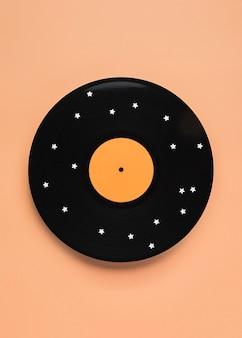Vue de dessus de la composition de vinyle noir avec des étoiles blanches