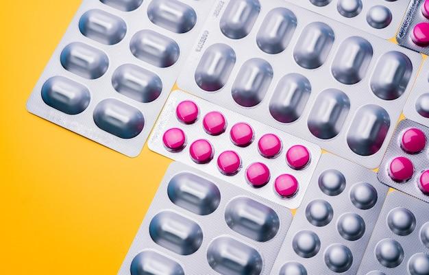 Vue de dessus comprimés ronds roses comprimés dans des plaquettes alvéolées et capsule dans une feuille d'aluminium argentée sur une surface jaune. industrie pharmaceutique.