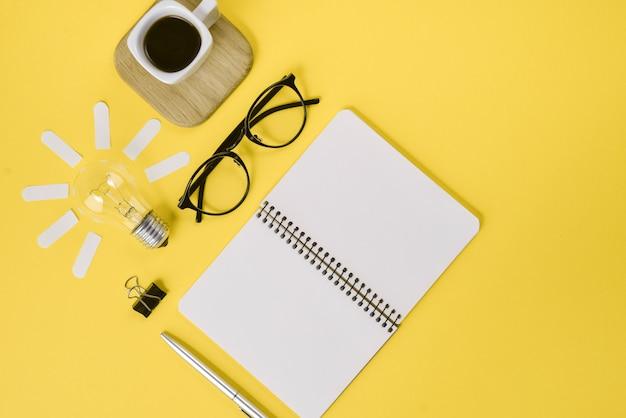 Vue de dessus concept créatif plat poser de bureau espace de travail style design fournitures de bureau avec stylo, bloc-notes, lunettes