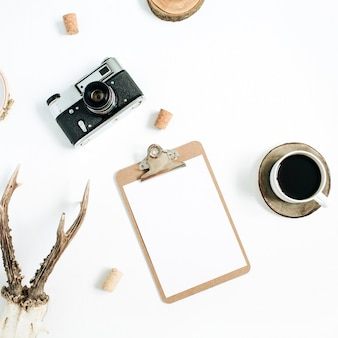 Vue de dessus, concept de photographe hipster plat laïc. appareil photo rétro, cornes de chèvre, presse-papiers et tasse de café du matin sur blanc.