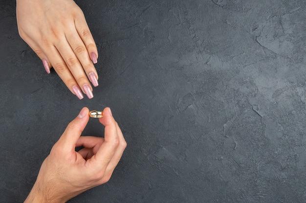 Vue de dessus concept de proposition de mariage main de l'homme plaçant l'anneau sur la main de la femme sur fond sombre avec lieu de copie