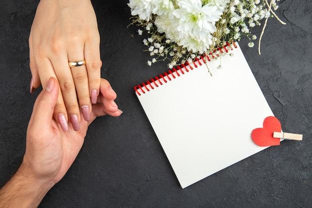 Vue de dessus concept de proposition de mariage main masculine tenant la main de femme avec cahier de fleurs anneau sur fond sombre