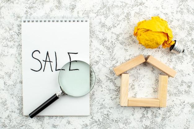 Vue de dessus concept publicitaire vente écrit sur bloc-notes lupa blocs de bois maison forme idée ampoule concept sur table grise