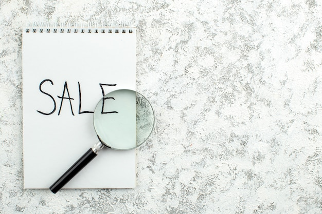 Vue de dessus concept publicitaire vente écrit sur le bloc-notes lupa sur fond blanc gris espace libre