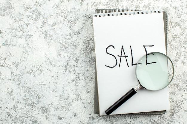 Vue de dessus concept publicitaire vente écrit sur le bloc-notes lupa sur le lieu de copie de table gris