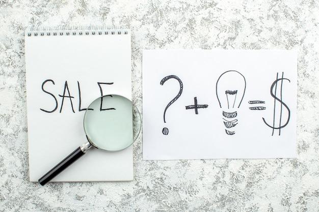 Vue de dessus concept publicitaire vente écrit sur le bloc-notes question lupa idée créative dollars dessin sur papier sur table grise