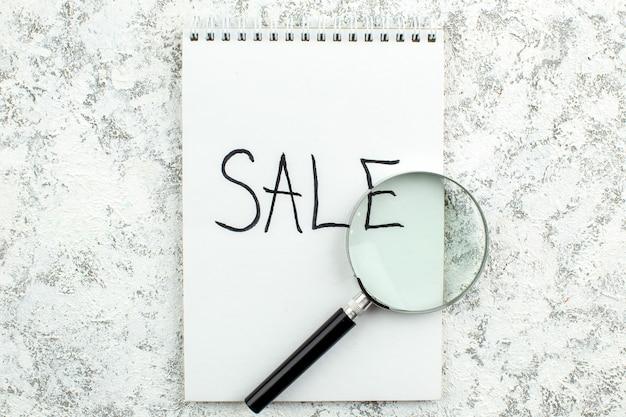 Vue de dessus concept publicitaire vente écrit sur ordinateur portable lupa sur fond blanc gris