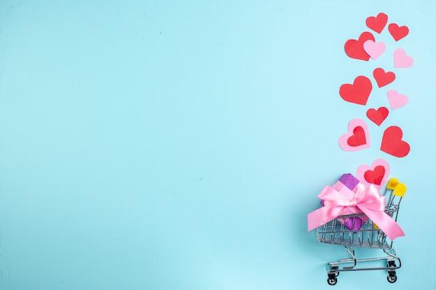 Vue de dessus concept saint valentin coeurs rouges et roses mini chariot avec cadeau sur fond bleu espace libre