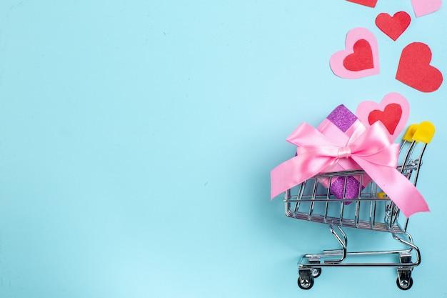 Vue de dessus concept de la saint-valentin coeurs rouges et roses mini chariot avec cadeau sur fond bleu avec lieu de copie