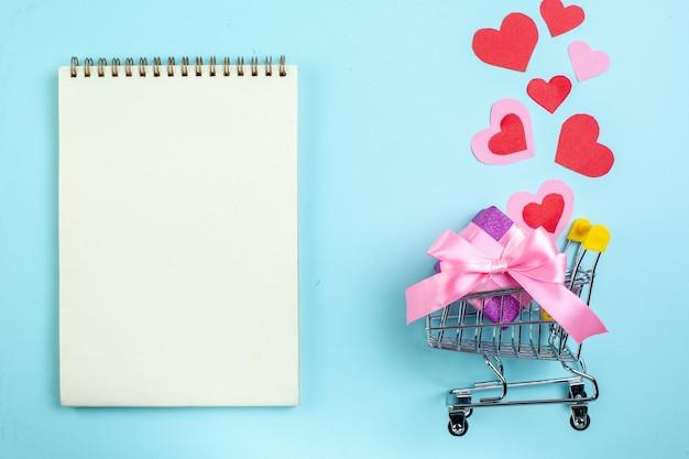 Vue de dessus concept de la saint-valentin coeurs rouges et roses pour ordinateur portable mini marché chariot avec cadeau sur fond bleu