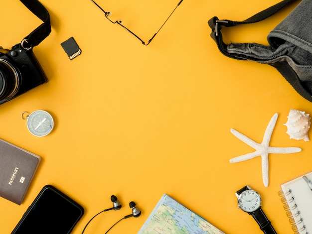 Vue de dessus concept de voyage avec des films de caméra rétro, téléphone, carte, passeport, boussole et tenue de voyageur sur fond jaune, essentiels touristiques, effet de ton vintage