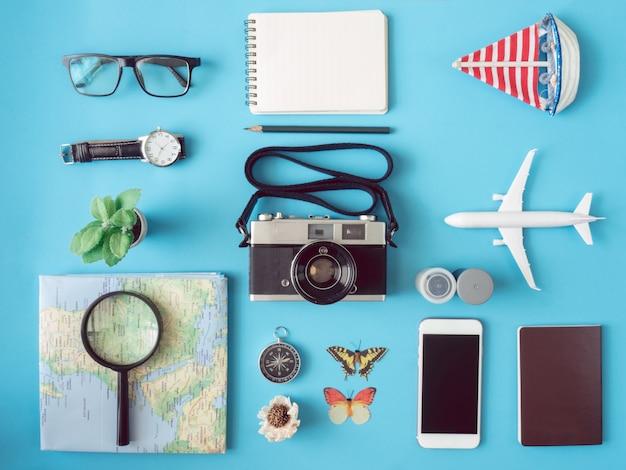 Vue de dessus concept de voyage avec des films de caméra rétro, téléphone, carte, passeport, boussole et tenue de voyageur sur la surface bleue, essentiels touristiques, effet de ton vintage