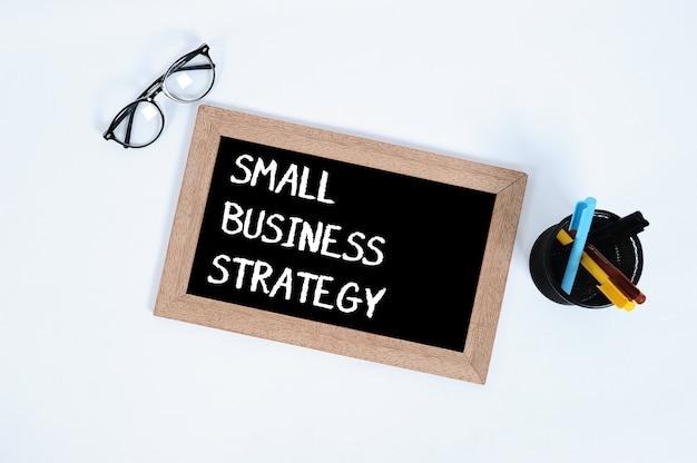 Vue de dessus conceptuelle de petite entreprise du texte de stratégie de petite entreprise écrit sur le tableau noir