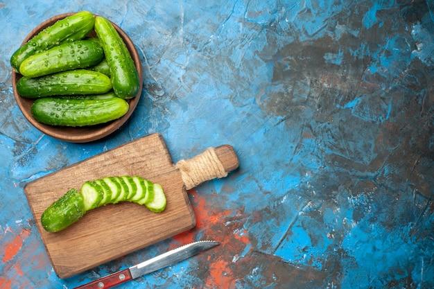Vue de dessus des concombres verts frais à l'intérieur de la plaque sur fond bleu