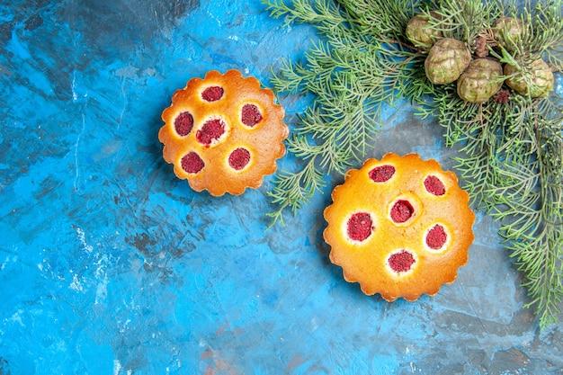 Vue de dessus des cônes de gâteaux aux framboises sur la surface bleue