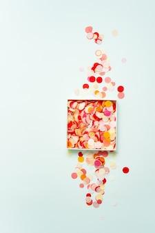 Vue de dessus de confettis de papier brillant dans une boîte sur fond pastel.