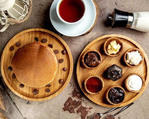Vue de dessus de la configuration du petit-déjeuner avec des crêpes, des confitures, de la crème au fromage et du beurre au chocolat