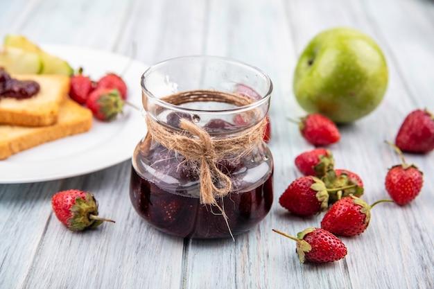 Vue de dessus de la confiture de fraises sur un bocal en verre avec des fraises fraîches isolé sur un fond en bois gris