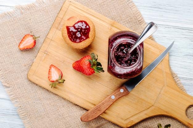 Vue de dessus de la confiture de fraises avec cupcake et fraise fraîche sur fond de bois blanc