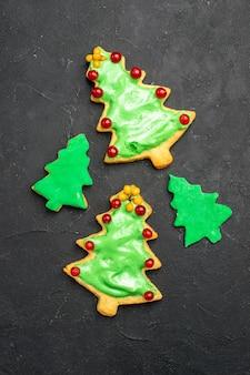 Vue de dessus des cookies d'arbre de noël sur une surface isolée sombre photo de nouvel an