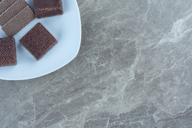 Vue de dessus des cookies au chocolat sur plaque blanche.