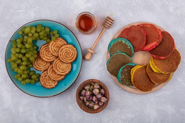 Vue de dessus des cookies aux raisins verts sur une plaque bleue avec des bourgeons séchés au miel et des crêpes multicolores sur un support sur un fond blanc