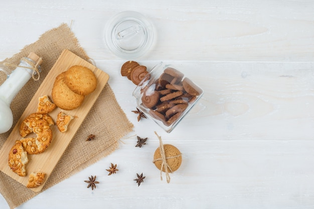 Vue de dessus des cookies bruns dans un bocal en verre avec une cruche de lait, des cookies sur une planche à découper et un morceau de sac sur une surface blanche