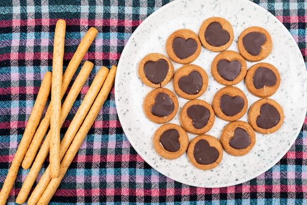 Vue de dessus des cookies avec du chocolat en forme de coeur en plaque