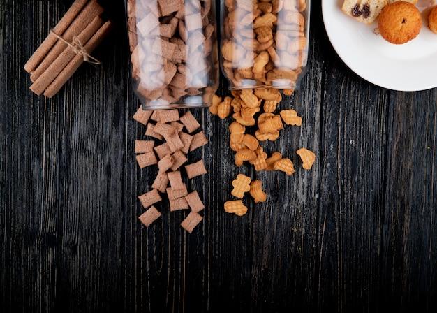 Vue de dessus des cookies de l'espace de copie dans un pot de cornflakes et bâtonnets de maïs sur un fond en bois noir