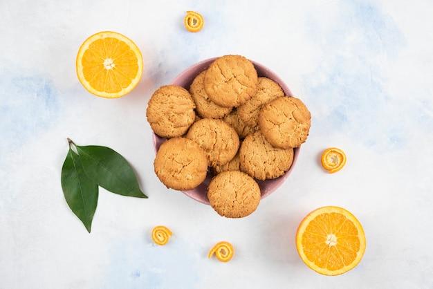 Vue de dessus des cookies faits maison sur planche de bois et oranges juteuses fraîches.