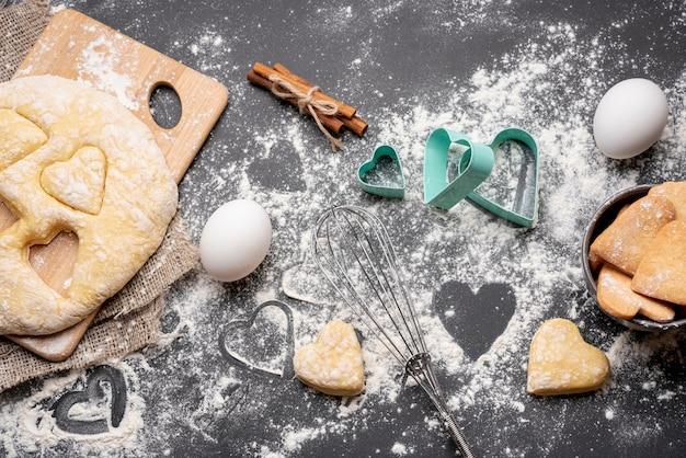 Vue de dessus des cookies de la saint-valentin avec des ustensiles de cuisine