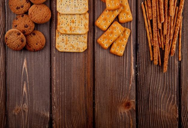 Vue de dessus copie des craquelins de l'espace avec des biscuits et des gressins sur une table en bois