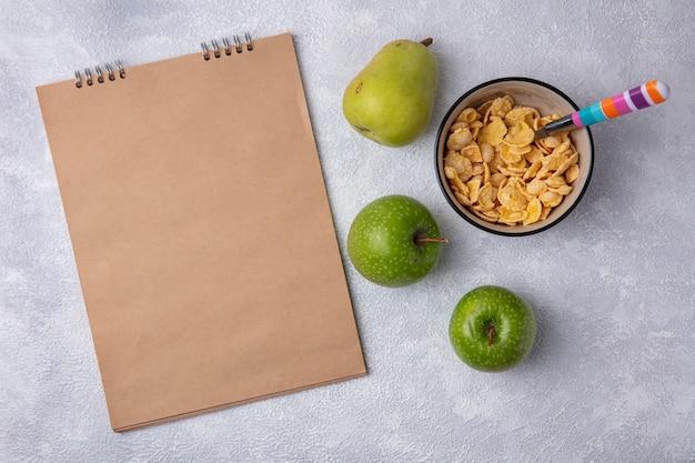 Vue de dessus copie espace bloc-notes beige avec pommes vertes cornflakes dans un bol avec une cuillère et poire sur fond blanc