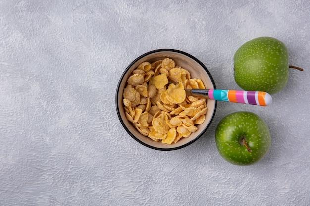 Vue de dessus copie espace cornflakes dans un bol avec cuillère et pommes vertes sur fond blanc