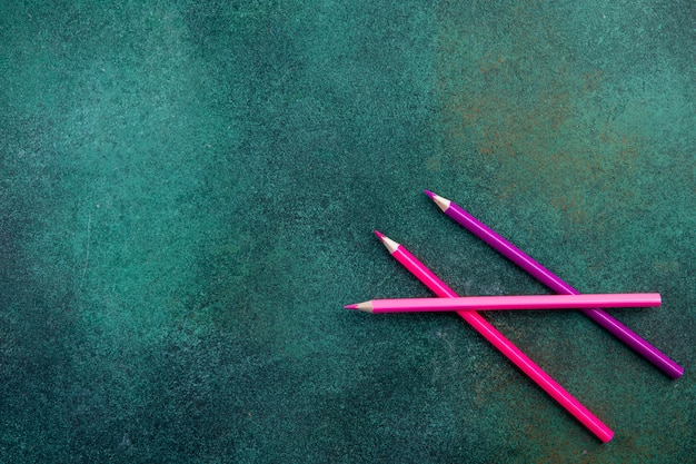 Vue de dessus copie espace crayons roses sur fond vert