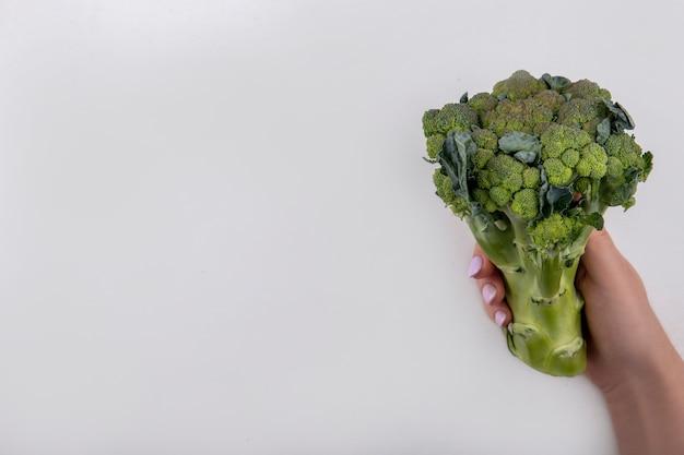 Vue de dessus copie espace femme tenant le brocoli dans sa main sur fond blanc