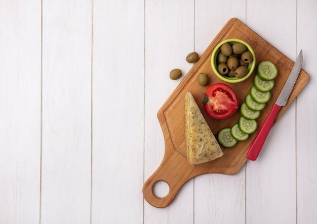 Vue de dessus copie espace fromage avec concombre tomate et olives avec couteau sur support sur fond blanc